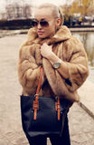 blond woman in luxurious fur coat and sunglasses Royalty Free Stock Image