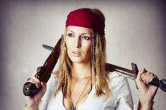 Sexy blond woman in pirat style. Fashion portrait of young sexy blond woman in pirat style with old handgun and medieval sword Royalty Free Stock Photography