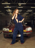 Sexy blond woman posing in a car garage Royalty Free Stock Photo