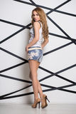 Sexy blond woman. Posing in fashionable jeans shorts Royalty Free Stock Photography