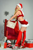 Sexy blond woman posing in frank Santa costume. Royalty Free Stock Images