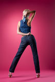 Sexy blond woman posing in jeans on pink Stock Photo