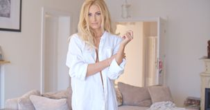 Sexy blond woman posing in a white shirt. In her living room giving the camera a provocative smile  side view Royalty Free Stock Photos
