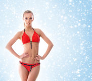 A sexy blond woman in a red swimsuit on a snowy background Royalty Free Stock Photography