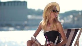 blond woman sitting on sun lounger on beach stock footage