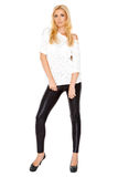 Sexy blond woman standing isolated. On white background  she wearing black pants and white shirt Stock Image