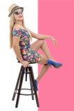 Sexy blond woman wearing short dress, sit on stool Stock Photos
