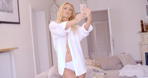 Sexy Blond Woman in White Taking Selfie Stock Images
