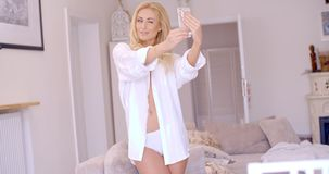 Sexy Blond Woman in White Taking Selfie Royalty Free Stock Image