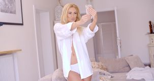 Sexy Blond Woman in White Taking Selfie Royalty Free Stock Photography