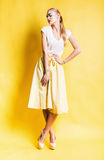 Sexy blond woman in yellow skirt Royalty Free Stock Images