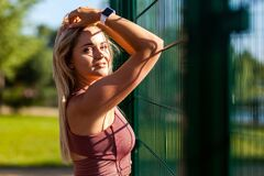Free Sexy Blond Young Woman In Sportive Top Standing Near Stadium Fence Outdoor, Touching Hair And Looking Seductively Royalty Free Stock Photo - 184903265