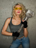 Blonde. With big metal hammer stock photography