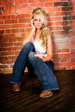 blonde against brick wall Stock Images
