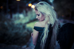 Sexy Blonde angel, young woman with black wings, autumn scene Royalty Free Stock Image