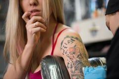Sexy blonde Aufstellung im Tätowierungsstudio Lizenzfreie Stockbilder
