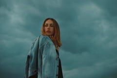 Sexy blonde behaarte junge Frau, die gegen dunklen schwermütigen Himmel im roten Licht der untergehender Sonne aufwirft Lizenzfreie Stockbilder