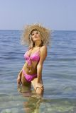 Sexy blonde in a bikini and straw hat. Royalty Free Stock Images