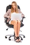 Sexy blonde boss working on a laptop Stock Images