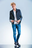 Sexy blonde boy wearing jeans and leather jacket while Royalty Free Stock Photo