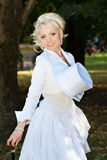 Sexy blonde bride in the park. Sexy bride with a cane and a hat-cylinder Stock Image