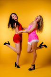 Blonde and brunette in the studio. Two young beautiful smiling women wearing pink clothing on yellow background. Blond and brunette girls royalty free stock image