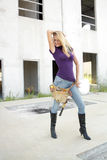 Sexy Blonde Construction Worker (3). A beautiful blonde with a tool belt and hardhat in front of a partially completed commercial building Royalty Free Stock Photo