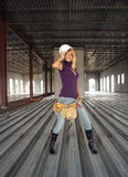 Sexy Blonde Construction Worker (5). A beautiful blonde with a tool belt and hardhat in a partially completed commercial building Royalty Free Stock Photos