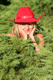 Blonde cowgirl. Beautiful blonde cowgirl in the countryside with red hat stock photography