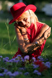 Blonde cowgirl. Beautiful blonde cowgirl in the countryside with red hat royalty free stock photography