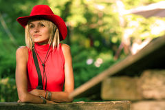 Blonde cowgirl. Beautiful blonde cowgirl in the countryside with red hat stock images