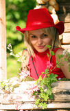 Blonde cowgirl. Beautiful blonde cowgirl in the countryside with red hat royalty free stock photos
