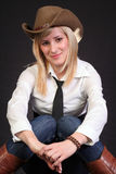 Blonde cowgirl. Beautiful blonde cowgirl in studio with cowboy hat stock photo