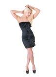 Sexy blonde Dame im schwarzen Kleid gegen Weiß Stockfoto