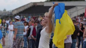Sexy blonde dancing with Ukrainian flag at an open music festival close-up, Beautiful girl at free rock concert in open stock video