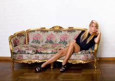 Sexy blonde die op bank gaan liggen stock afbeeldingen