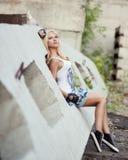 Sexy blonde in een korte rok die concrete blokken zitten royalty-vrije stock fotografie