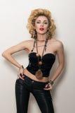 Sexy blonde erwachsene Frau in der schwarzen Korsett- und Lederhose Lizenzfreies Stockbild
