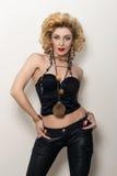 Sexy blonde erwachsene Frau in der schwarzen Korsett- und Lederhose Lizenzfreie Stockfotos