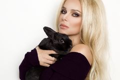 Blonde female model , standing on a white background. And holding a rabbit stock photo