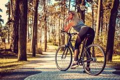 Sexy blonde Frau auf einem Fahrrad Stockbilder