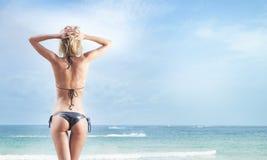 Sexy blonde Frau, die auf dem Strand sich entspannt Stockfotografie
