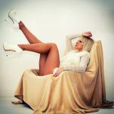 Sexy blonde Frau, die auf Lehnsessel liegt Lizenzfreies Stockfoto