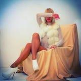Sexy blonde Frau, die auf Lehnsessel liegt Stockfoto