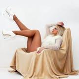Sexy blonde Frau, die auf Lehnsessel liegt Stockbilder