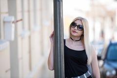Sexy blonde Frau, die auf Lichtmast sich lehnt Stockbilder