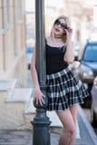 Sexy blonde Frau, die auf Lichtmast sich lehnt Lizenzfreie Stockfotos