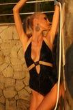 Sexy blonde Frau, die Dusche auf Sonnenuntergangstrand nimmt Stockbild