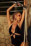 Sexy blonde Frau, die Dusche auf Sonnenuntergangstrand nimmt Lizenzfreie Stockbilder