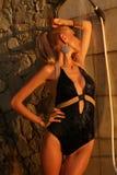 Sexy blonde Frau, die Dusche auf Sonnenuntergangstrand nimmt Lizenzfreies Stockfoto